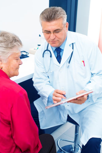 Older Woman Patient Talking to Male Doctor with ClipBoard
