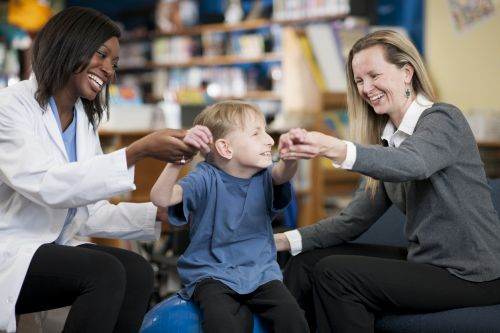 A mother and physical therapist are helping a child with a physical disability work on his motor skills by sitting on an inflatable ball.