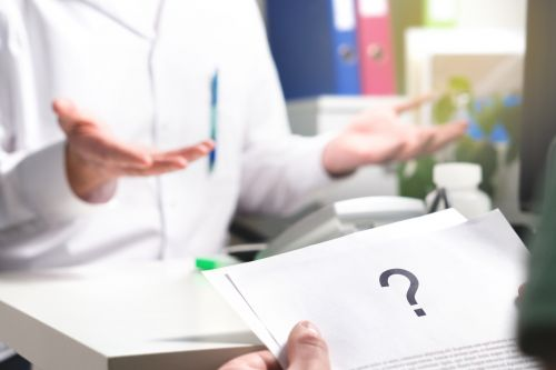 Patient reading health care document with question mark.