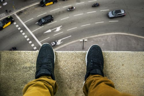 Two feet at the edge of a rooftop of a high building.