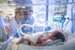 Worried young couple looking at their premature newborn in an incubator with oxygen at neonatal intensive care unit.
